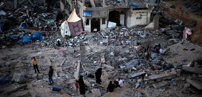 Una familia gazatí, entre los escombros de su casa destruida por bombas israelíes. REUTERS/Suhaib Salem