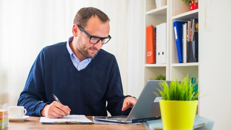 An employee looks at a laptop screen.