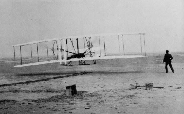 Βόρεια Καρολίνα, 17 Δεκεμβρίου του 1903: Η πρώτη πτήση των αδελφών Ράιτ. O Γουίλμπουρ έτρεχε παράλληλα με το αεροπλάνο, ενώ ο Όρβιλ το οδηγούσε. Κανείς δεν θα πίστευε το επίτευγμα τους, αν δεν είχαν φωτογραφηθεί. Σε αυτούς τους δύο Αμερικανούς αποδίδεται η εφεύρεση και κατασκευή του πρώτου επιτυχημένου  αεροπλάνου στον κόσμο και η πραγματοποίηση της πρώτης ελεγχόμενης μηχανικά προωθούμενης πτήσης.