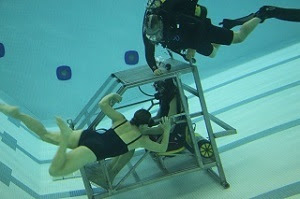 a woman in a swimsuit practices underwater rescue from a submerged vehicle while a SCUBA-clad instructor watches