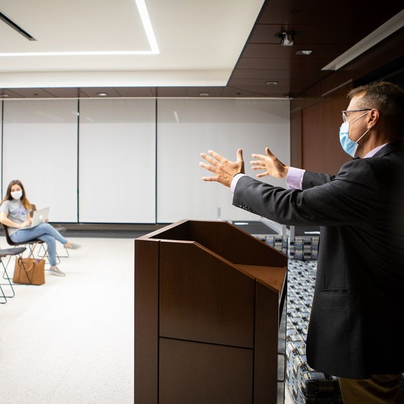 Students and a professor demonstrate current physical distancing and face covering best practices in a classroom in Capen Hall in July 2020