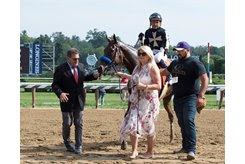 Barb Perry of Cicero Farms leads Marley's Freedom into the winner's circle at Saratoga Race Course