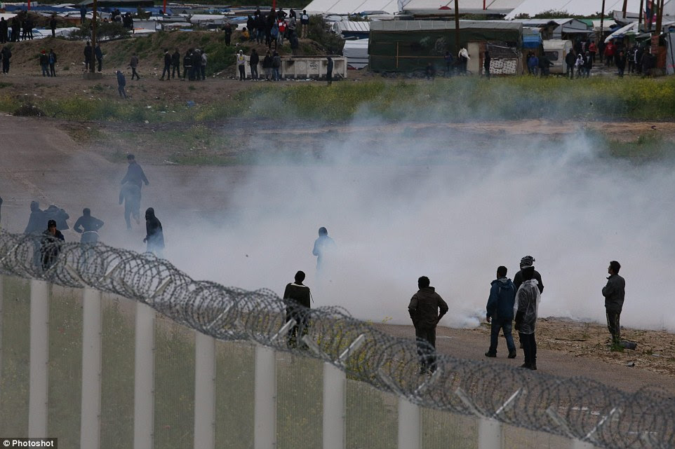 Like a warzone: Clouds of tear roll over the Jungle refugee camp after migrants started throwing bricks at motorists caught up in ten-hour tailbacks on the roads to Calais on Monday
