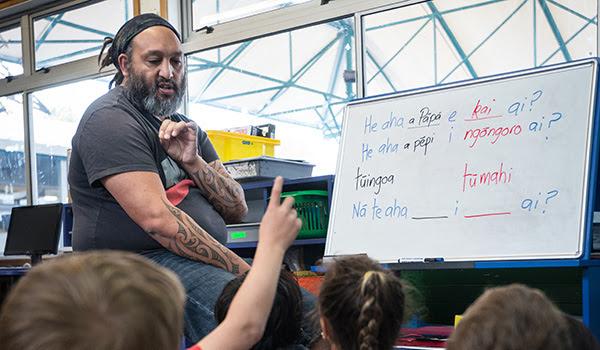 A teacher teaching kids te reo Māori at a whiteboard. One child's hand is raised.