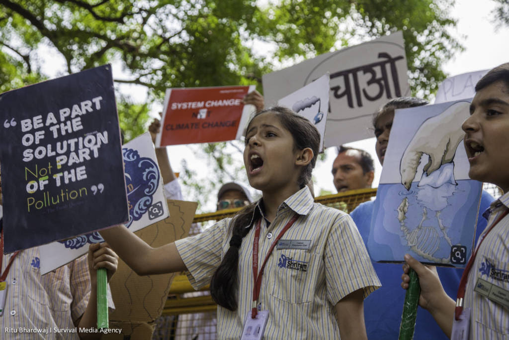 "A young girl holds a sign that says ""be a part of the solution not the pollution"" in New Dehli (India) surrounded by other impassioned children"