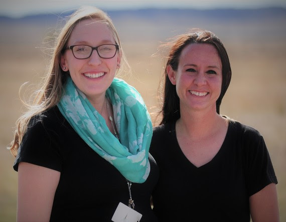 Valerie Bruce and Sara Reed pose next to each other outside Valerie's school with the Wyoming prairie in the background.