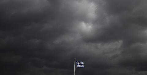 La bandera griega ondea sobre la Acrópolis de Atenas, bajo un cielo cubierto de nubes de tormenta. REUTERS/Yannis Behrakis