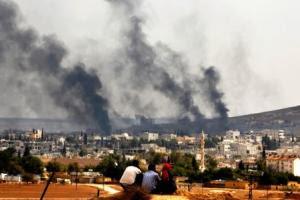 Kurdish refugees look at their town of Kobani covered…