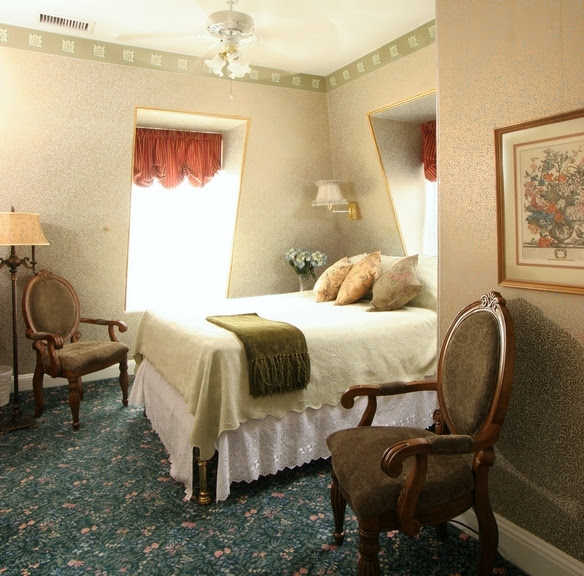 Picture of a Queen sized antique oak bed in a cheery room with yellow walls and rich green carpet.