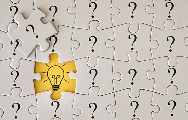 Puzzle pieces with question marks and a light bulb.