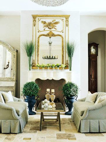 Symmetrical rooms lend a structured air, ideal for formal entertaining. The look is achieved by first determining the axis. In this living room, the fireplace is the axis. Plants and candlesticks on the fireplace and coffee table mirror each other. A loveseat is placed on each side of the axis. The arched doorway and armoire also balance each side.