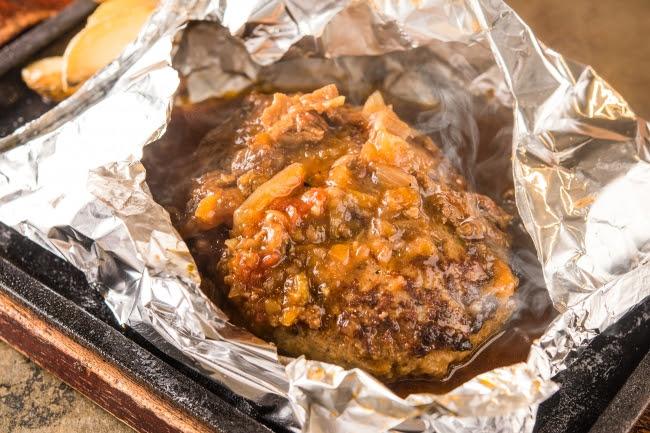 自家製ミートデミグラスの包み焼きハンバーグ。 熟成牛を練りこむことで凝縮された肉の旨みと溢れる肉汁を楽しんでいただけます。