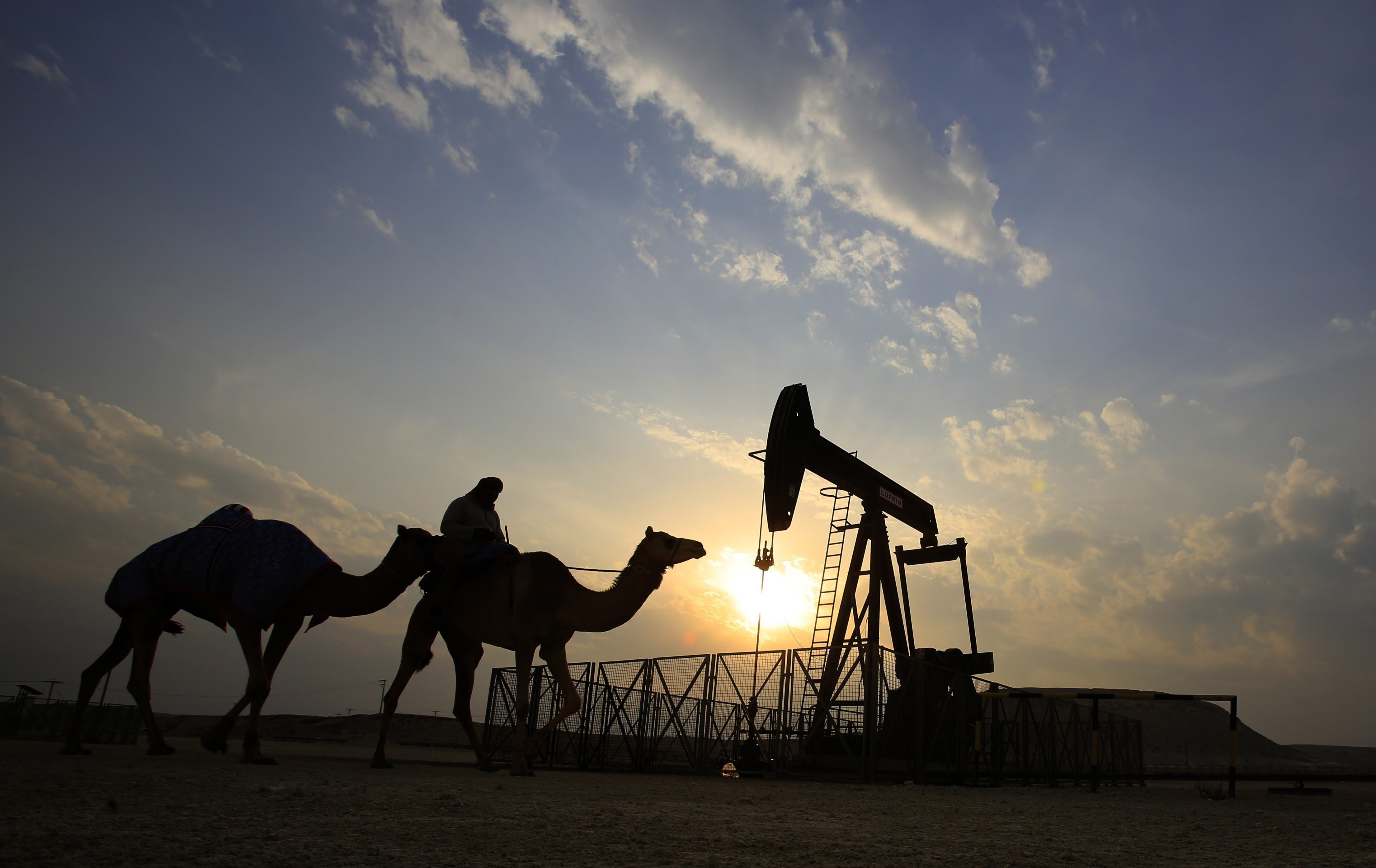 A man rides a camel through the desert oil field and winter camping area of Sakhir, Bahrain. OPEC said production decreased in March by 153,000 barrels a day to an average of 31.93 million barrels a day.
