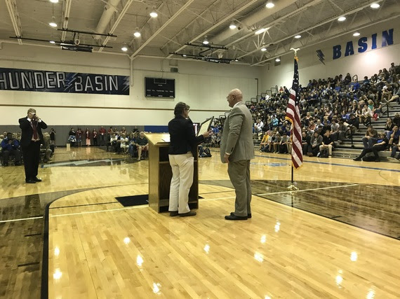 Campbell County School District Superintendent #1, Dr. Boyd Brown, stands at the podium in Thunder Basin High School gym full of students, staff, and community members while a staff member reads the Governor's proclamation.