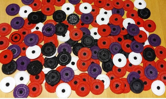 Colour phot showing a pile of stitched poppies in white, red, black and purple.