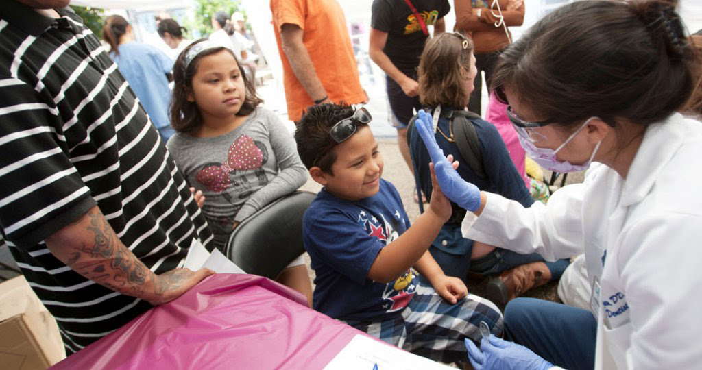 Child high-fiving a dental technician during a free clinic