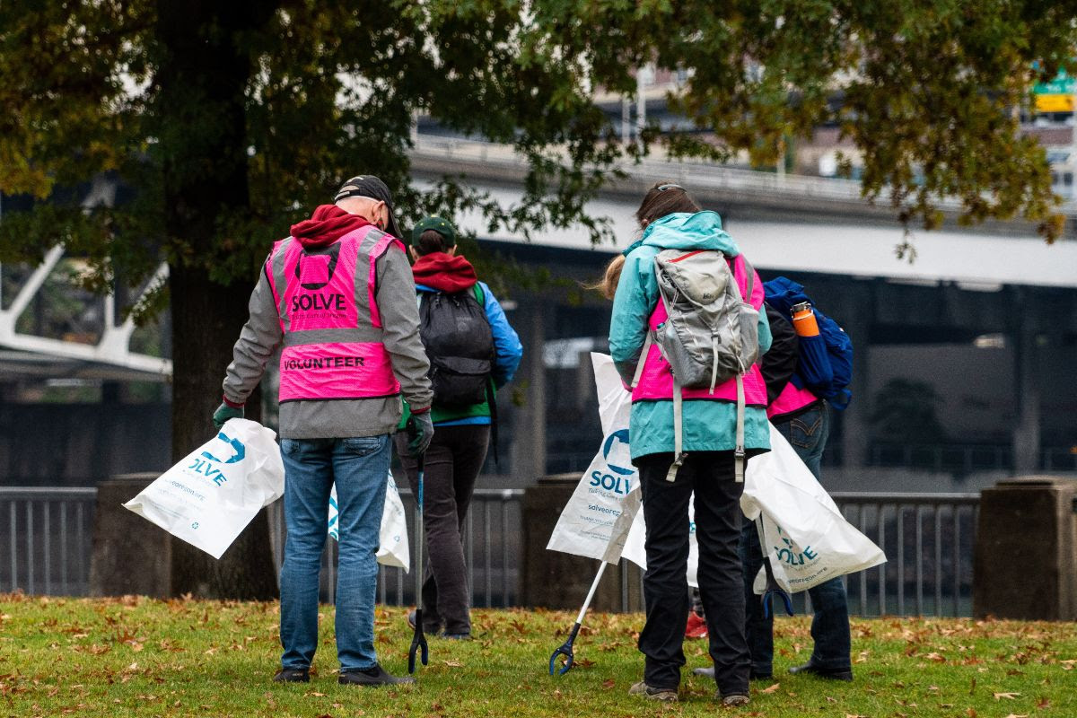 Four volunteers wear safety vests and hold trash bags and trash pickers in Waterfront Park