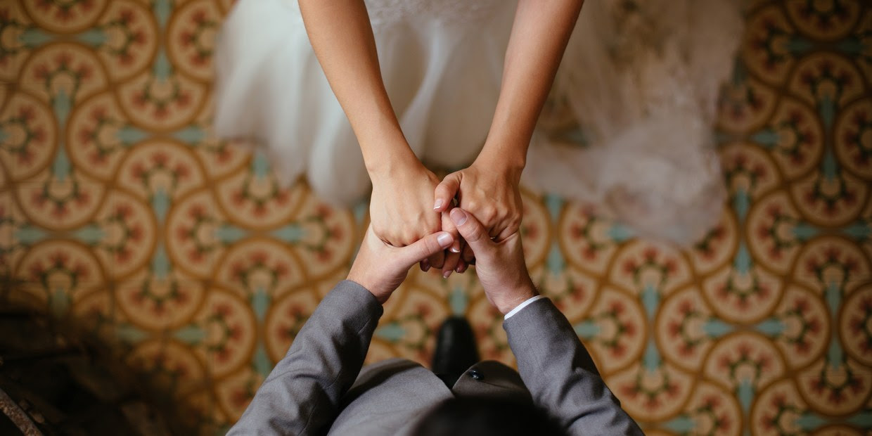 Overhead view of bride and groom holding hands