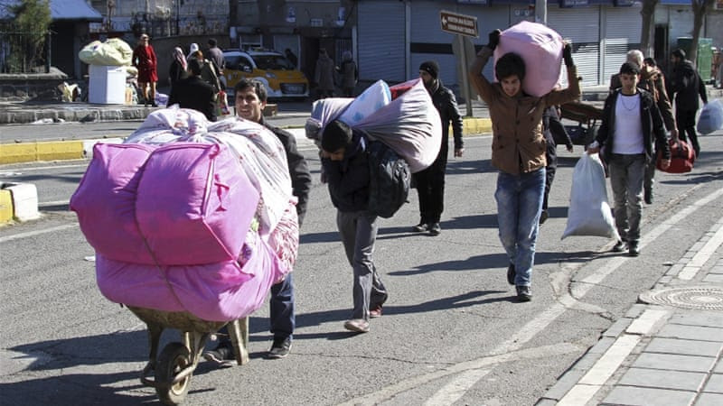 Residents carry their belongings as they flee from Sur district, which is partially under curfew, in the Kurdish-dominated southeastern city of Diyarbakir [Reuters]