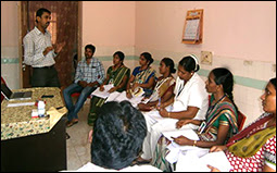 The figure shows a group of people in India listening to a discussion.