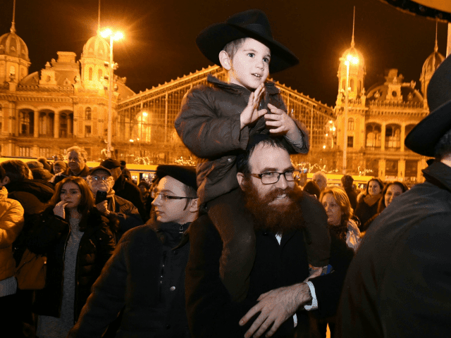 Hungarians from the Jewish community take part in a ceremony during which a giant Menorah is lit to mark the start of Hanukkah celebrations on December 12, 2017 at the Western square in the center of Budapest Hanukkah commemorates the re-dedication of the holy temple in Jerusalem after the Jews' â?¦