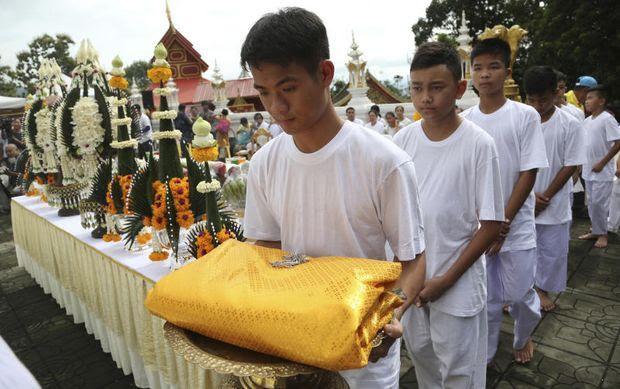 Các em dâng y cúng dường Đức Phật