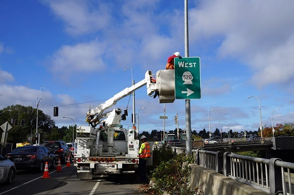 A construction worker in a lift installs a directional sign on a pole on the side of a road.