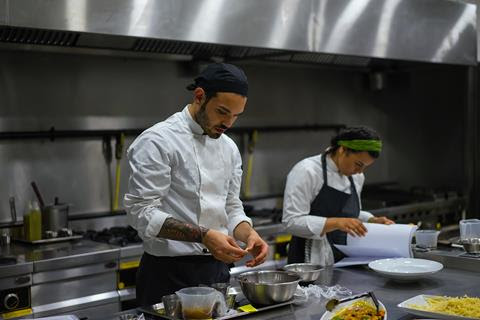 Two chefs work in a large kitchen