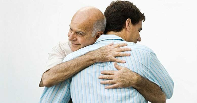 hijo abrazando a su padre anciano feliz fondo claro
