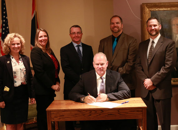 Governor Mead sits at a desk to sign the proclamation with State Superintendent Jillian Balow and four principals standing behind him.