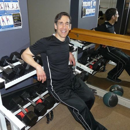 Man sitting on rack of weights