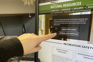 """Someone's finger pointing to the """"replace lost certificate"""" button on the DNR recreational safety webpage"""