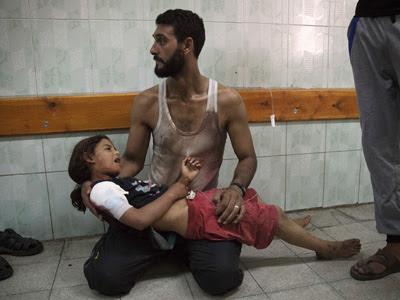 Un hombre espera atención médica para su hija, herida en el bombardeo de la escuela de la ONU. REUTERS/Finbarr O'Reilly