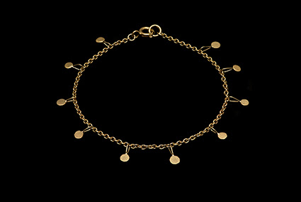 A photograph of a golden necklace by Gillian Finlay, displayed on a solid black background.
