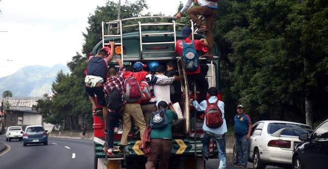 Migrantes hondureños que tratan de alcanzar EEUU, subidos a un autobús a su paso por la capital de Guatemala. REUTERS/Edgard Garrido
