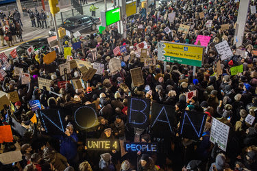 Demonstrators gathered outside Kennedy Airport in New York on Saturday to protest the treatment of refugees and others from the seven countries named in President Trump's executive order.