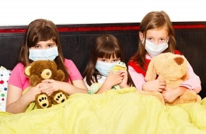 Sick children in bed wearing medical masks because of infection with influenza virus.