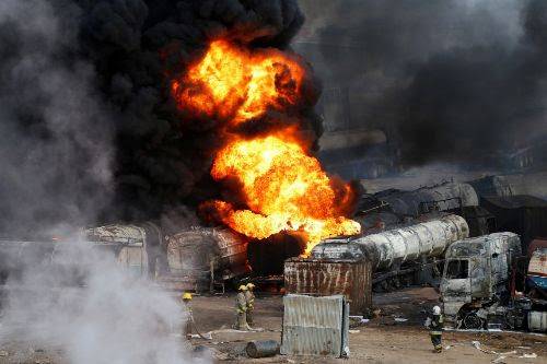 FILE PHOTO: Smoke and flames rise from fuel trucks after an overnight...