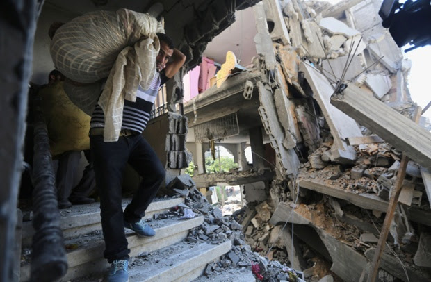 Palestinians carry belongings in a house after it was hit by an Israeli missile strike in Gaza City.