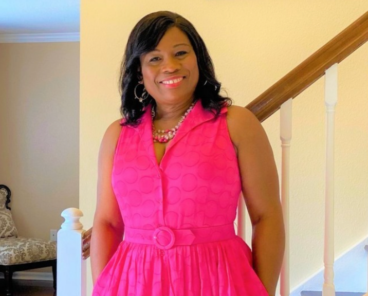 A black woman with curly black hair and a pink dress. She is smiling