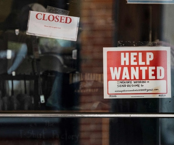 Help-wanted signs on a glass door