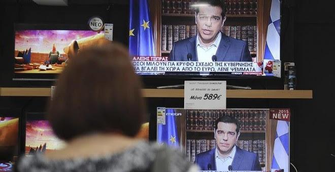 Una mujer observa en una tienda en Atenas el discurso televisado del primer ministro griego, Alexis Tsipras. - EFE