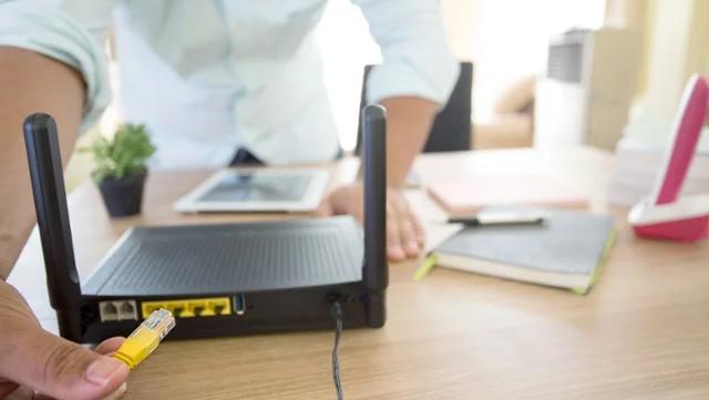 Mano de una persona conectando un cable a un enrutador de internet.