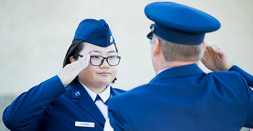 A female student in uniform salutes a uniformed officer.