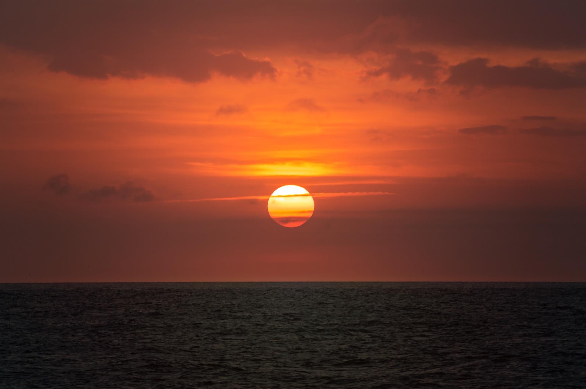 The sun sets over a vast ocean