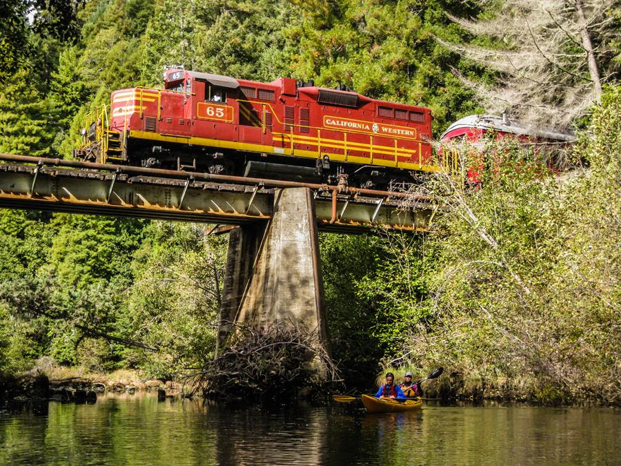The Mendocino County Skunk Train crosses a bridge while passing over a river