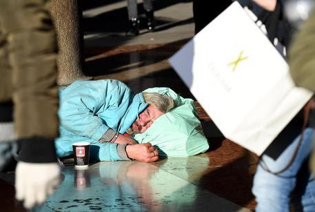 Un clochard addormentato in una strada del centro di Milano © ANSA