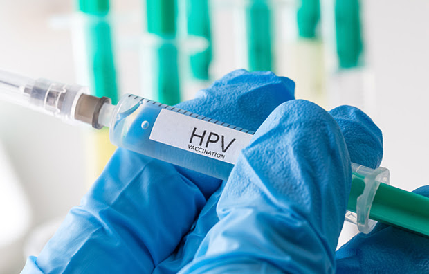 """A closeup of a hand in a medical glove holding a vaccine that says """"HPV vaccination""""."""