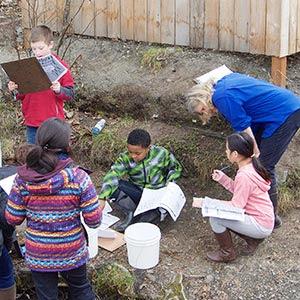 Children and teach examining creek ecosystem