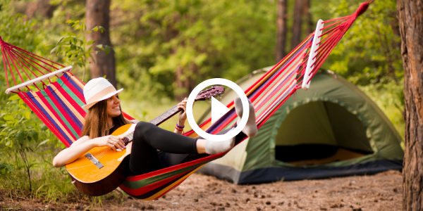 girl playing guitar in hammock by tent, video link